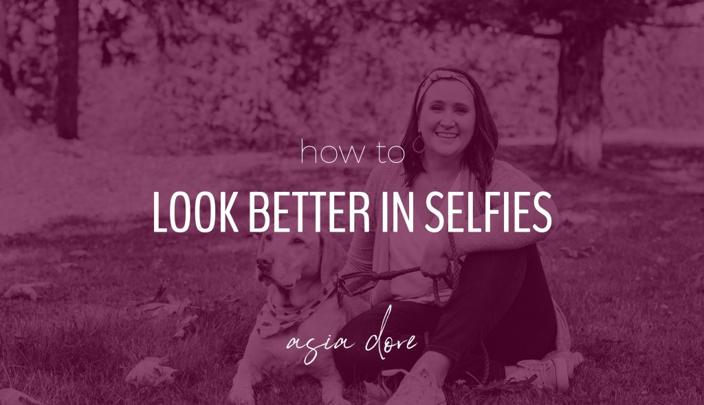 A smiling woman sitting on the ground in a park next to her yellow labrador retriever with text - how to look better in selfies