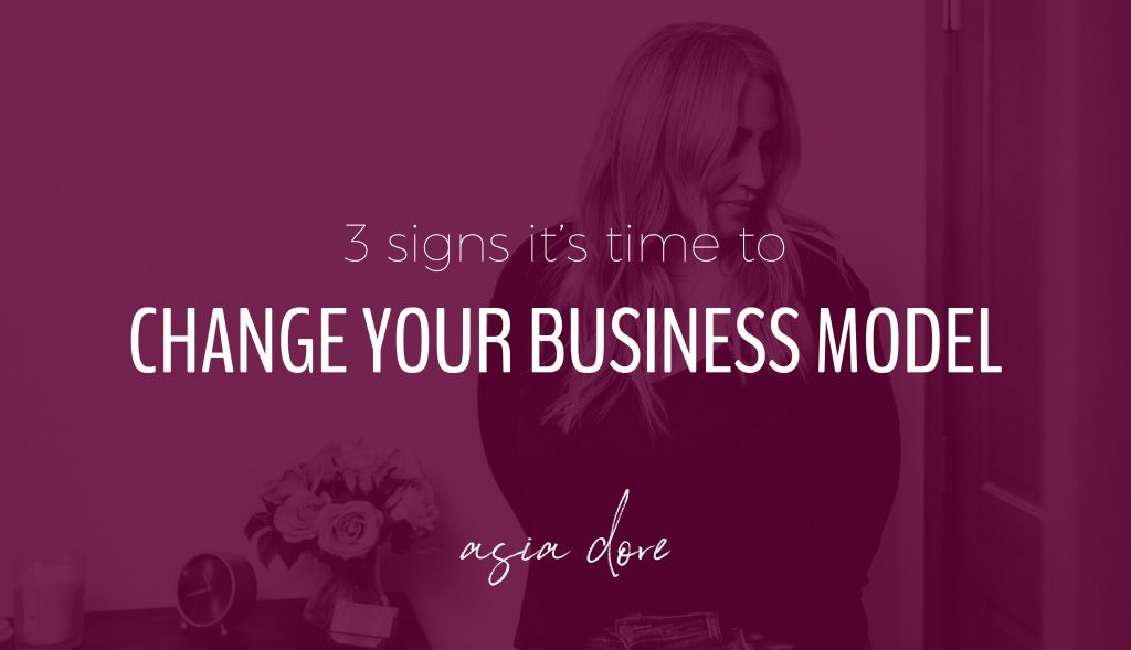 Blonde woman standing next to a desk with a clock and vase of flowers. She's smiling slightly and looking down. With text - 3 signs it's time to change your business model