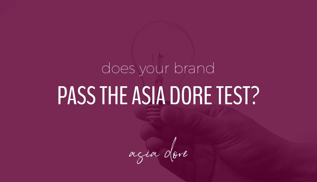 A hand holding an unlit lightbulb with text - does your brand pass the asia dore test?