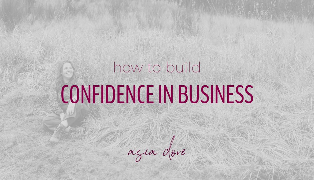 A smiling woman sits cross-legged in a grassy field with text - how to build confidence in business.