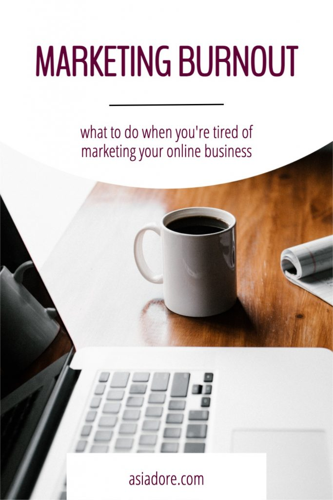 A notbook, coffee, and laptop sitting on a desk next to a bright window with text - Marketing burnout, what to do when you're tired of marketing your online business