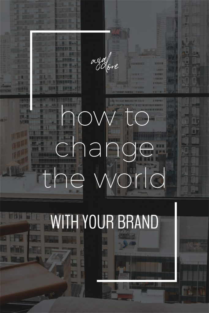 A city window view of tall downtown buildings with text - how to change the world with your brand