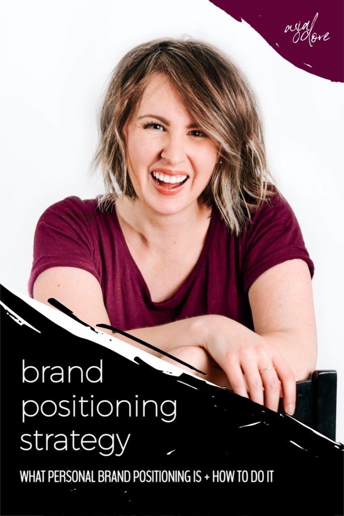 Smiling woman looking directly at the camera - her wrists are crossed over the back of her chair. With text - brand positioning strategy, what personal brand positioning is and how to do it