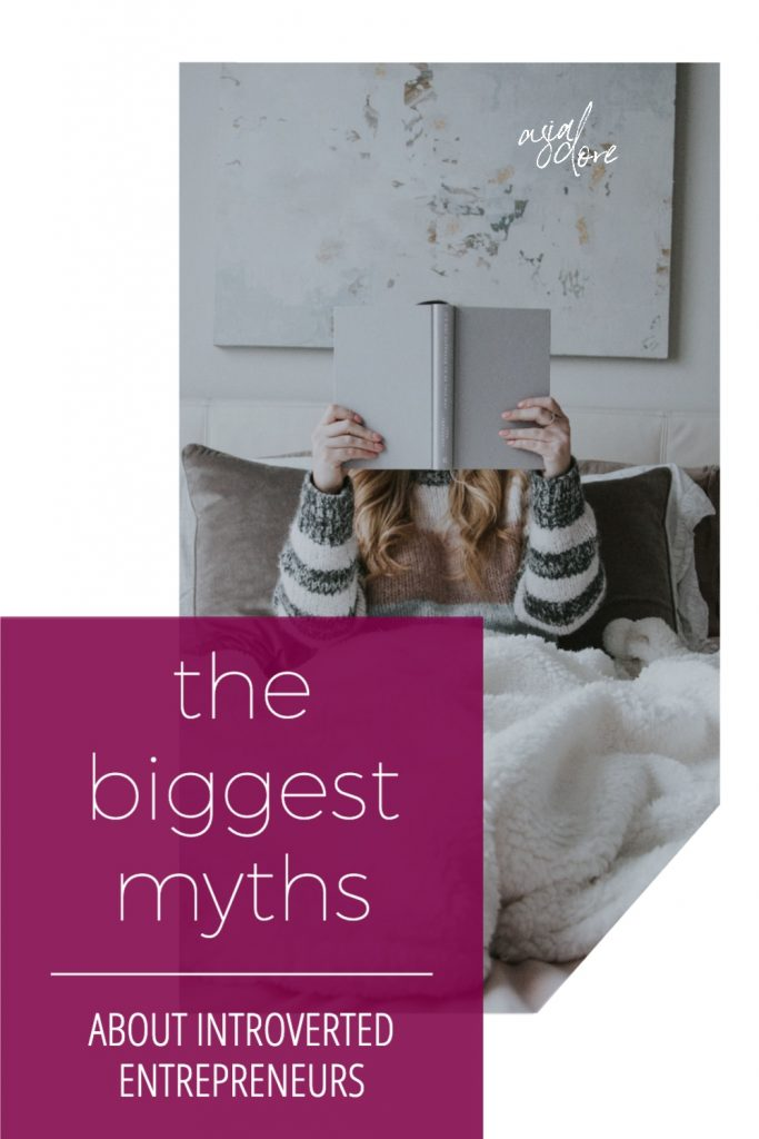 A blonde woman laying in bed under a cozy blanket. Her face is covered by the book she's holding up. With text - the biggest myths about introverted entrepreneurs.