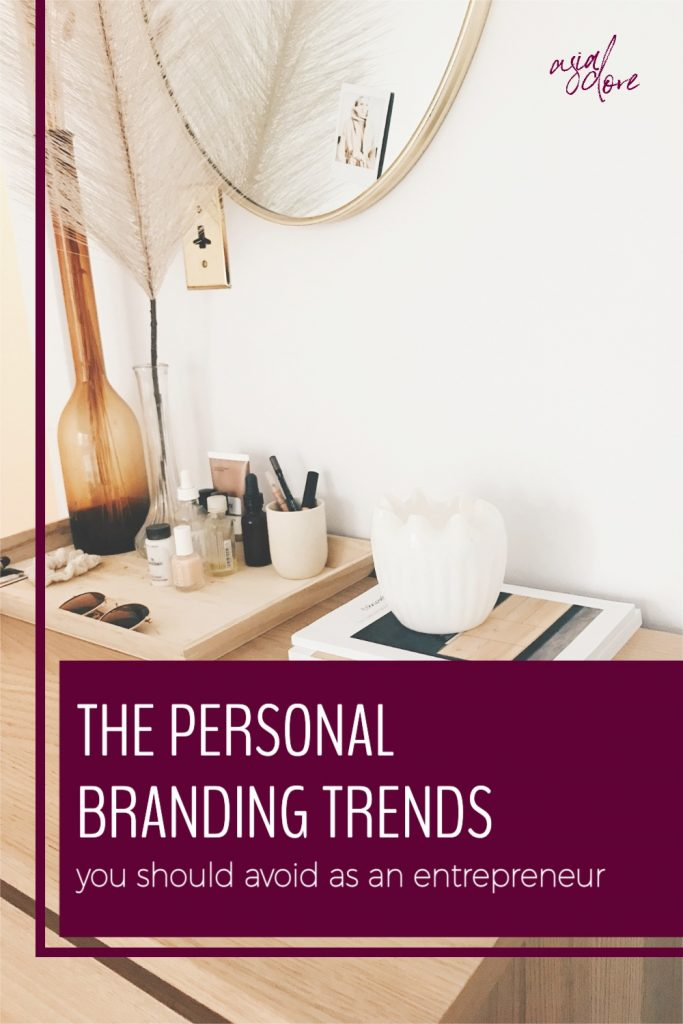 A chic desk  with magazines, flowers, sunglasses, makeup, and a candle with text - the personal branding trends you should avoid as an entrepreneur