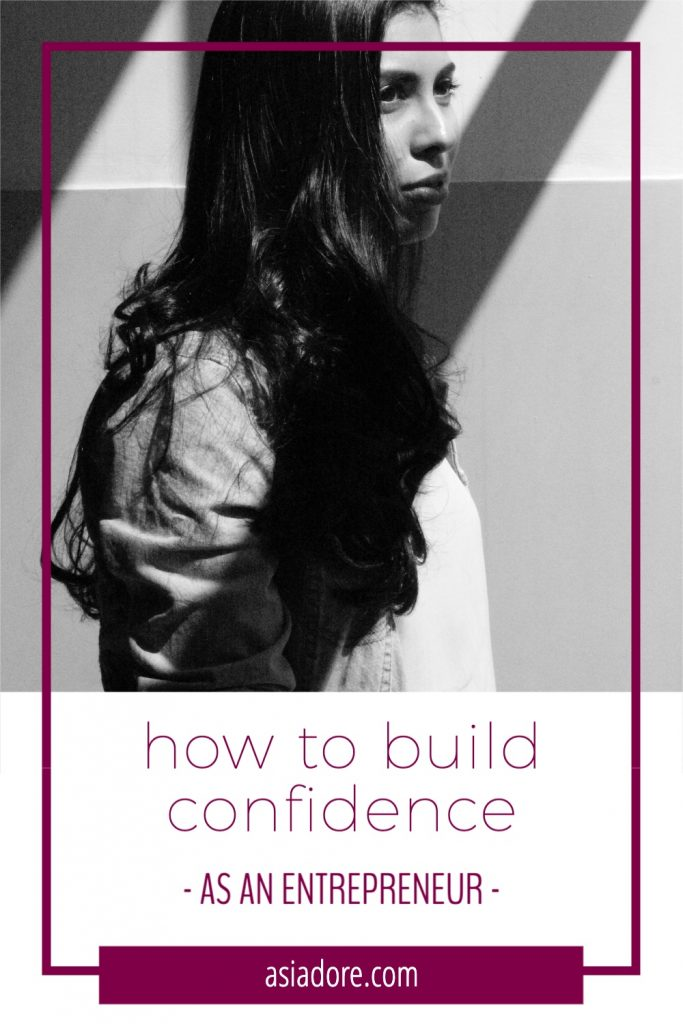 A long-haired woman stands next to a wall with a small smile on her face and looks off camera. With text - how to build confidence as an entrepreneur